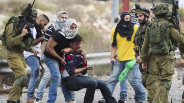 Undercover Israeli police officers and Israeli soldiers detain a wounded Palestinian demonstrator, being pulled up, during clashes near Ramallah, West Bank.