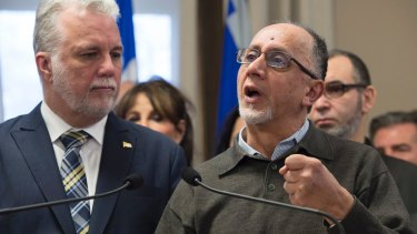 Benabdallah Boufeldja, right, co-founder of the Islamic cultural centre, responds to reporters questions as Quebec Premier Philippe Couillard, left, looks on.