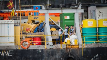 Police point to a crane on a barge where a man died on Wednesday.
