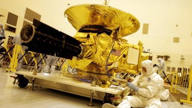 Technicians work on the payload for the New Horizons mission to Pluto on Friday, November 4, 2005, at the Kennedy Space Centre at Cape Canaveral.