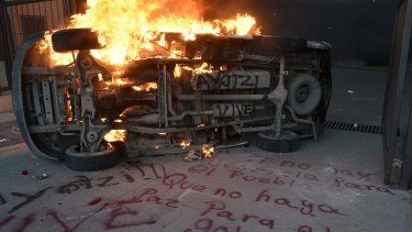 "A car burns next to graffiti reading ""If there is no justice for the people, shall be no peace for the government"" during a protest demanding for justice in the case of the 43 missing students, outside the State Government headquarters in Chilpancingo, Guerrero State"