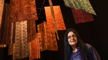 Senior curator of Indigenous art Judith Ryan with batik banners by artists including Emily Kame Kngwarreye in <i>Who's Afraid of Colour?</i> at the at the National Gallery of Victoria.