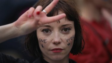 A protester makes a peace sign in an anti-Brexit rally in front of the Houses of Parliament in London.