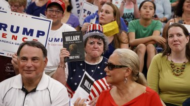 A Trump supporter holds a copy of Dolly Kyle's recently published expose on Hillary Clinton at a campaign rally in New Hampshire.