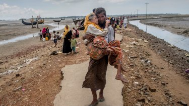 A Rohingya Muslim man Abdul Kareem walks towards a refugee camp carrying his mother Alima Khatoon after crossing over from Myanmar into Bangladesh.
