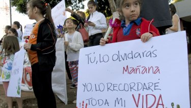 "A young girl holds a sign reading in Spanish ""You'll forget it, me, I will remember it for the rest of my life,"" at a demonstration in front of the Attorney General's office in Ciudad del Este, Paraguay in May."