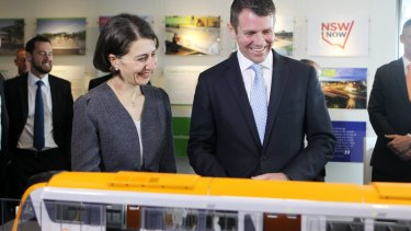 All aboard: Mike Baird and Gladys Berejiklian study a model of the new rolling stock at this week's announcement.