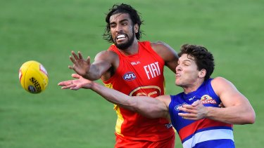 Tom Nicholls of the Suns and Will Minson of the Bulldogs fight for the ball.