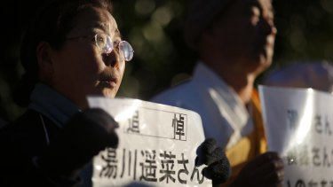 "A woman, holding a sign stating: ""In memory of Mr Haruna Yukawa,"" takes part in a vigil outside the Japanese prime minister's residence in Tokyo on Sunday."