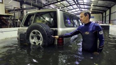 UNSW researcher Grantley Smith moves a four-wheel drive with his fingertip after it begins to float in a floodwater simulation.