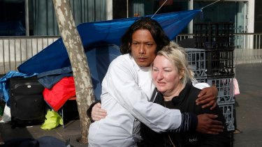 Residents of the Martin Place tent city embrace before packing up.