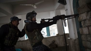Iraqi Federal Police shoot toward Islamic State militant positions during fighting in western Mosul, Iraq, on Thursday.