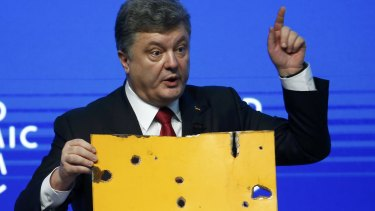 Ukrainian President Petro Poroshenko holds a fragment of a bus he says shows a Russian rocket attack while addressing the World Economic Forum in Davos.