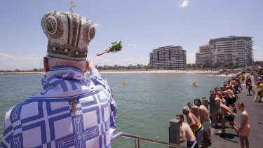 His Grace Bishop Ezekiel of Dervis throws the cross into the water during The Blessing of the Waters at Princes Pier in Port Melbourne.