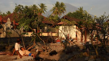 A man and his child looking towards Mount Agung in Purwakerti, in a safe zone