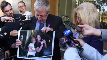 Mark and Faye Leveson show a photo of their son Matthew Leveson with his partner Michael Atkins outside the Coroner's Court on Friday.