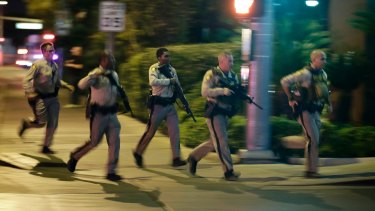 Police run to cover at the scene of a shooting near the Mandalay Bay resort and casino on the Las Vegas Strip.