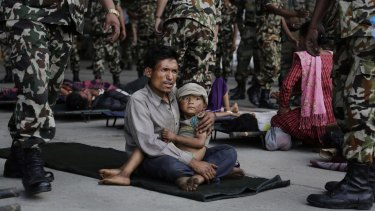 A man sits with a child on his lap as victims of Saturday's earthquake wait for ambulances after being evacuated to Kathmandu, Nepal.
