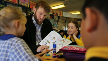 Michael Hanaghan shows a Latin textbook to Haberfield Public School students (from left) Elke Chapin, Mila Ossowaka and Jazz Lee.