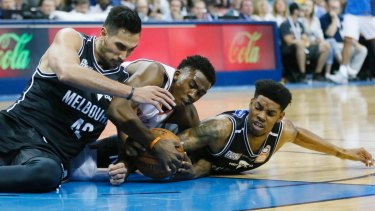 Grounded: Melbourne United's Tai Wesley (left) and Casper Ware take on Oklahoma City Thunder guard Semaj Christon (centre).