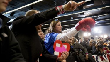 A member of the audience wears boxing gloves as she cheers before Democratic presidential candidate Hillary Clinton arrives to speak at her caucus night rally at Drake University in Des Moines, Iowa.