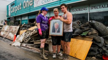 BRISBANE. NEWS. BRISBANE TIMES. Photograph taken by Michelle Smith on Friday 14th January, 2011. Lisa Hooper with daughter Alexandra, 23, and son Nicholas, 16, holding a photo of their grandfather JT Hooper. The picture was the only thing untouched by the rising flood waters of the Bremer which made it all the way to the roof of the building.