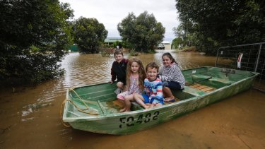 Jake Baker, Ivy Baker, Logan Farrar and Layla Baker use a boat to get from their front door on Simmie Road, Echuca.