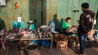 A dried-fish vendor at a morning market in Vientiane.