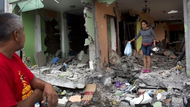 Karina Vera leaves her brother's house after recovering a cooking pot and other usable items one week after the devastating earthquake on the outskirts of Pedernales, Ecuador.