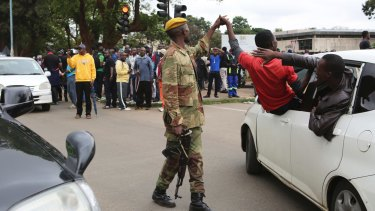 A man holds the hand of a soldier as euphoric crowds march on the streets of Harare, demanding the departure of President Robert Mugabe.