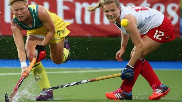 Tough conditions: water skids off the turf as Georgia Nanscawen of Australia hits a a shot away from Hollie Webb of England.