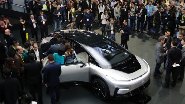 People gather around the Faraday Future's FF 91 electric car at CES 2017, in Las Vegas.