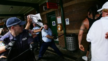 Craig Campbell, pictured with his baton, fends off violent youths during the Cronulla riots in 2005.