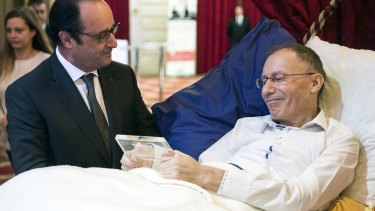 French President Francois Hollande talks with the laureate Claude Emmanuel Triomphe, laying on a bed as he was injured in the November 13 Paris attacks.