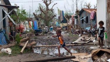 Young children walk through debris in Vanuata after Cyclone Pam hit in 2015.