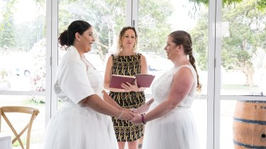 Marriage celebrant Elizabeth Trevan officiates at the wedding of Kylie and Lisa Caro.