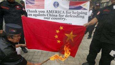 Protest leader Elly Pamatong burns a Chinese flag near the US embassy in Manila on Monday.
