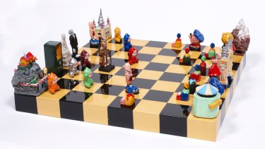 MOS2011/1-1:33. 2001. The Luna Park Chess Set by local artist Peter Kingston is a playful evocation of Sydney?s historic fun park. It consists of a playing board, timber storage box (not pictured) and 32 chess pieces, and is both a work of art and a playable chess set. Opposing sides are denoted by red and green felt on the bottom of each of the pieces. Individual chess pieces depict major features of the park, including historic rides, slot machines and traditional side show elements: pawns are laughing clowns or kewpie dolls; castles are depicted as rides including the Rotor, River Cave and Noah?s Ark; knights feature characters Popeye and Crazy Crooner driving dodgem cars; the red team?s king is Luna Park?s entrance gate and facade, while the green team?s king is a skeleton from the Ghost Train, perhaps hinting at the darker side of Luna Park?s history. For full details refer to the Vernon database. Many more photographs of the chess set are available on disc held by Collections & Access ? see Senior Librarian. Luna Park chess set by Peter Kingston. For Spectrum's objects story.