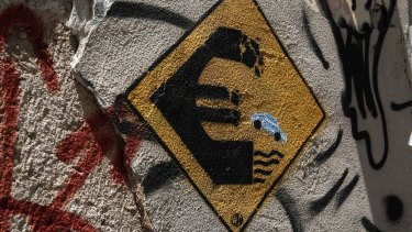 Graffiti on wall of abandoned house in Athens depicts car driving off a Euro sign into water.