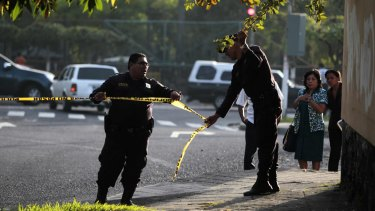Police secure a crime scene after a bus driver was killed by suspected gang members  on Monday.