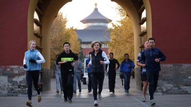 Foreign Affairs Minister Julie Bishop jogs with her security entourage at the Temple of Heaven in Beijing on Monday.