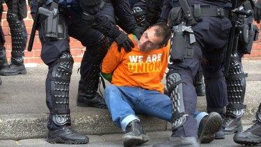Riot police restrain a protester.
