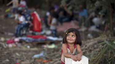 A Syrian migrant girl leans on a border stone on the Serbian border with Hungary near the village of Horgos.