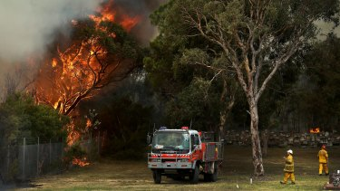 Fire crews backburn around the cemetery, near Hospital Road in Kurri.