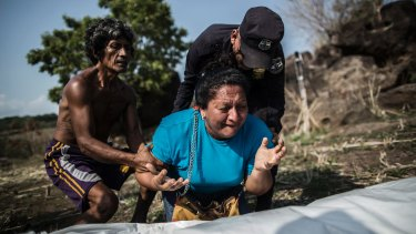 A woman mourns over the body of her brother, found in a clandestine grave, in a rural area of El Salvador.