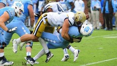 Heavy hitter: Adam Gotsis tackles North Carolina quarterback Marquise Williams.