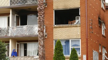 A woman looks out from her balcony under the apartment damaged by fire last night in Lakemba.