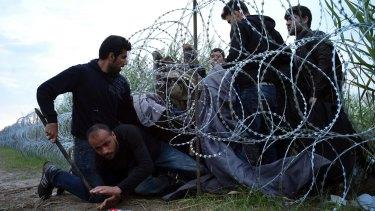 Syrian refugees cross into Hungary underneath the border fence on the Serbian border near Roszke.