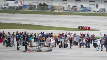 People stand on the tarmac at Fort Lauderdale-Hollywood International Airport after a gunman opened fire.