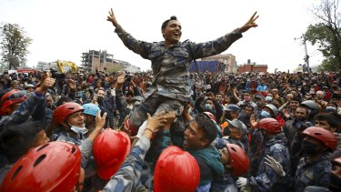 Members of the Nepalese Armed Police Force carry their officer and cheer after successfully rescuing the young survivor.